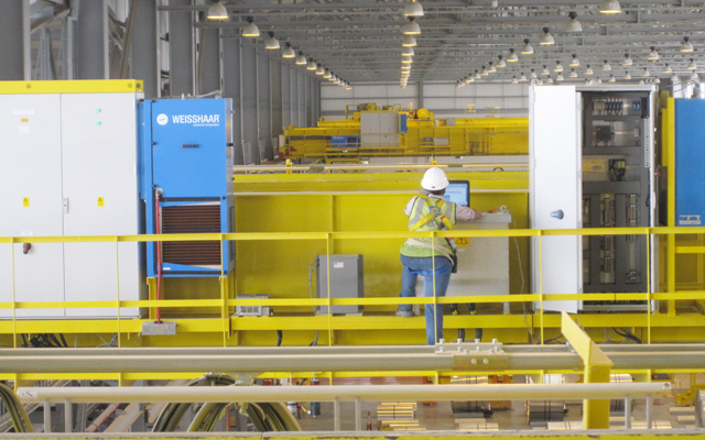 Engineer using control station of automated crane in Oman aluminium rolling plant